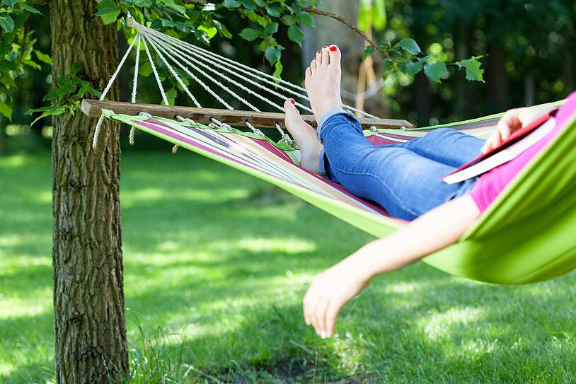 Young lady resting on hammock with book summer
